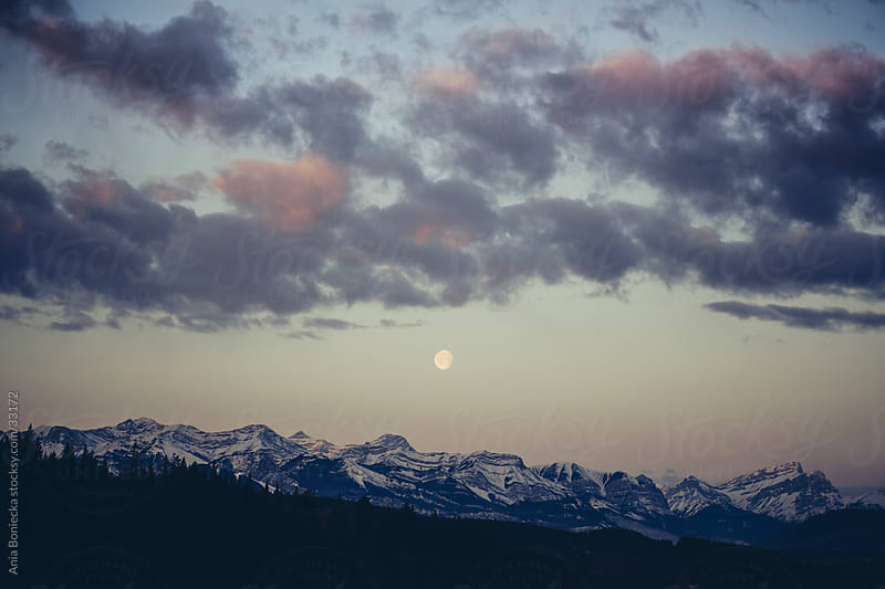 The moon over the mountains at sunrise by Ania Boniecka for Stocksy United