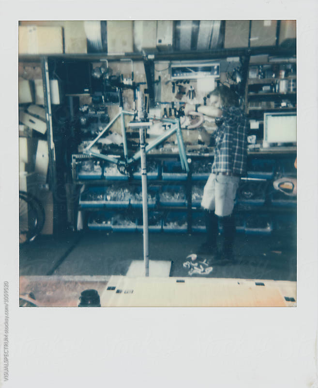 Polaroid of Male Hipster Assembling Fixed Gear Bicycle in Bike Repair Shop by Julien L. Balmer for Stocksy United