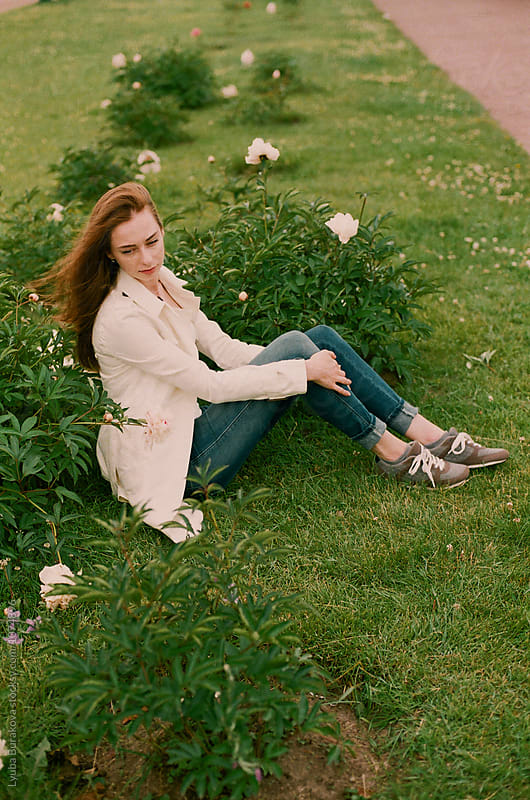 Young woman sitting on the grass by Liubov Burakova for Stocksy United