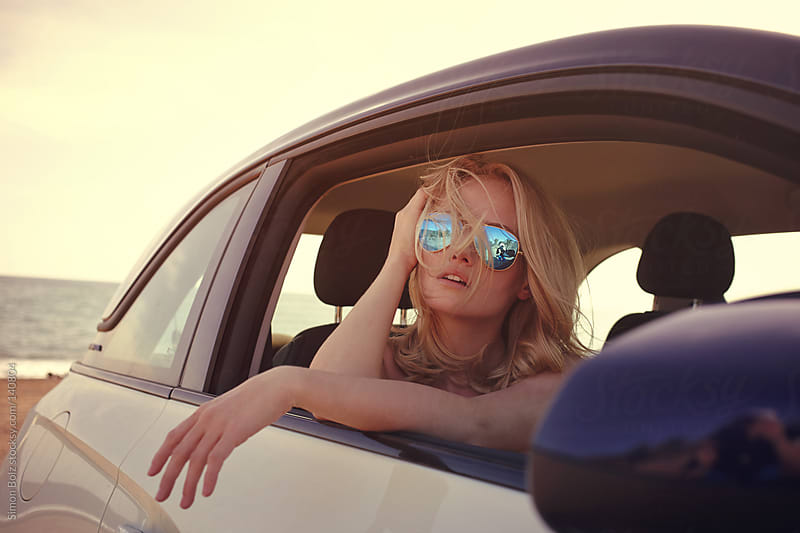 Blonde female with sunglasses looks through car window sitting on passenger seat by Simon Bolz for Stocksy United