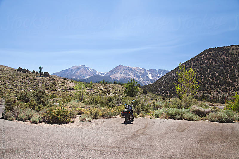 motorcycle parked on side of the road with Yosemite National Park in the background by Natalie JEFFCOTT for Stocksy United
