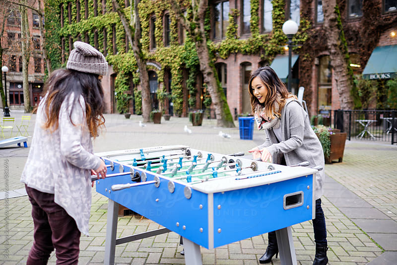 Beautiful Asian women having fun playing foosball outdoor by Suprijono Suharjoto for Stocksy United