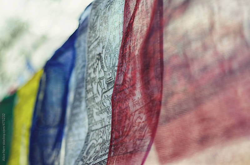Closeup of a line of Buddhist prayer flags with mantras by Alice Nerr for Stocksy United