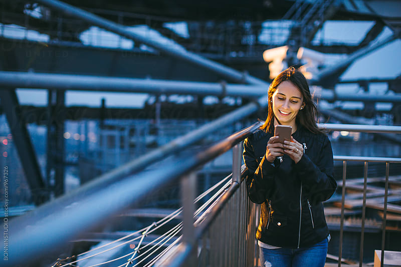 Smiling woman using her phone from rooftop at night. by BONNINSTUDIO for Stocksy United
