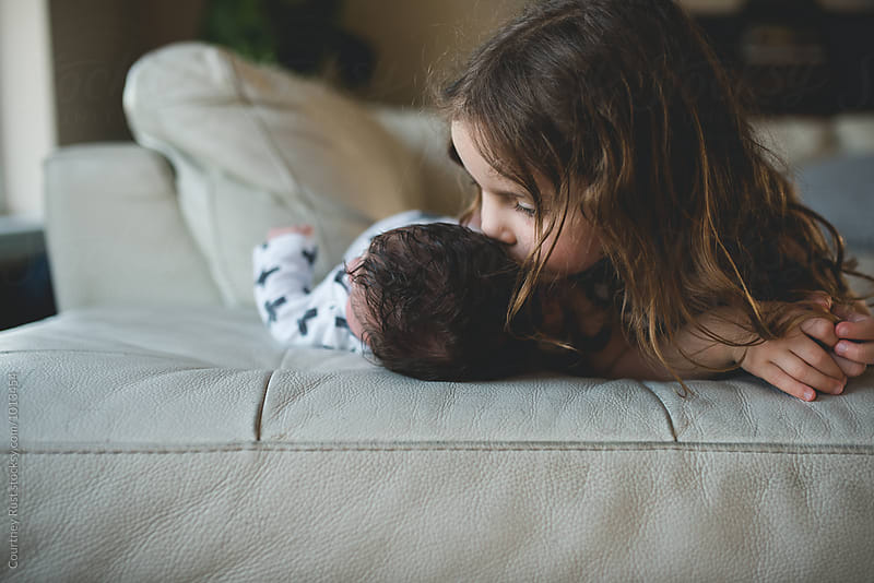 Sister giving new baby kiss  by Courtney Rust for Stocksy United