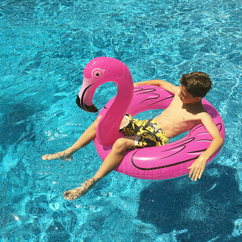 A Boy Floating On A Flamingo Float In A Summer Swimming Pool by ALICIA BOCK for Stocksy United