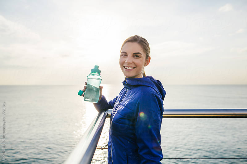 Portrait of a woman drinking water after running. by BONNINSTUDIO for Stocksy United