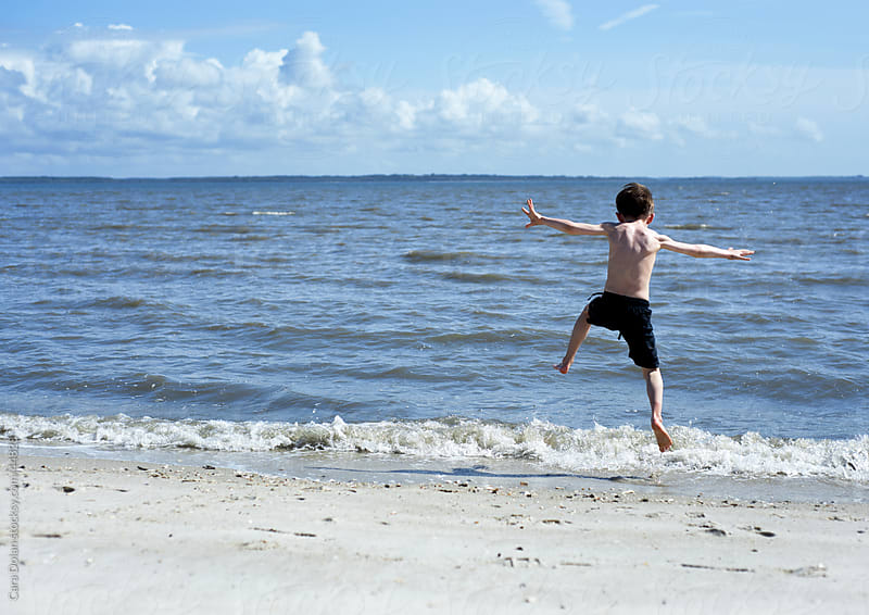 Boy in swim trunks leaps at the edge of an ocean wave by Cara Dolan for Stocksy United