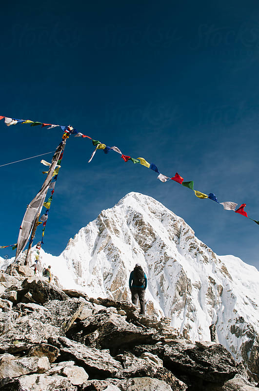 Female trekker beneath prayer flags, Kala Pattar (5,545 metres), Everest Region, Sagarmatha National Park, Nepal. by Thomas Pickard for Stocksy United