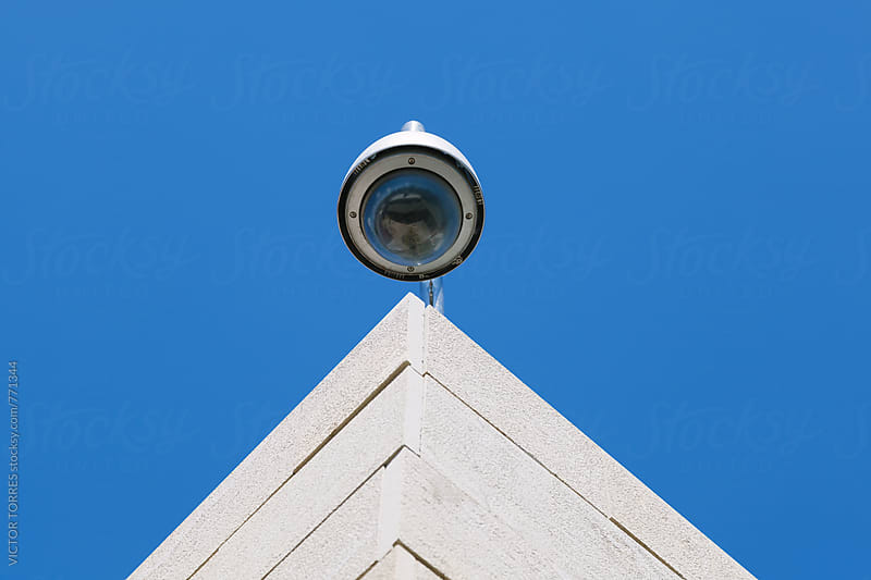 Security Cam on a Top Roof Against a Radiant Blue Sky by VICTOR TORRES for Stocksy United