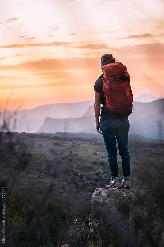 Female hiker with backpack on a rocky outcrop watching the sunset by Micky Wiswedel for Stocksy United