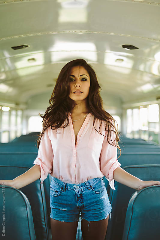 Young pretty woman on an empty bus by Dalton Campbell for Stocksy United