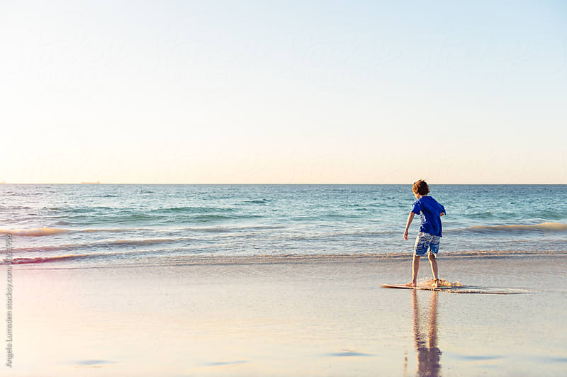 Boy riding a skim board at the beach at sunset by Angela Lumsden for Stocksy United