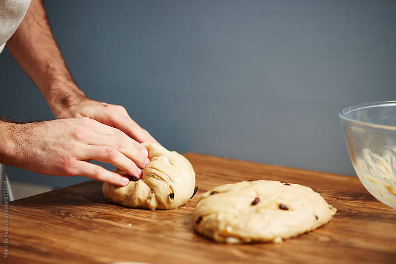 Chef rolling panettone's dough on wooden table by Martí Sans for Stocksy United