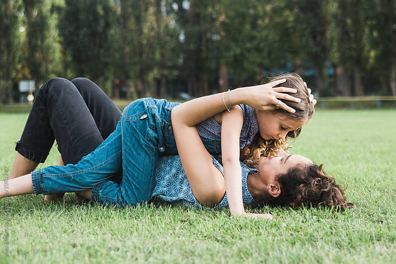Mother and her little daughter embracing on the grass by Irina Efremova for Stocksy United