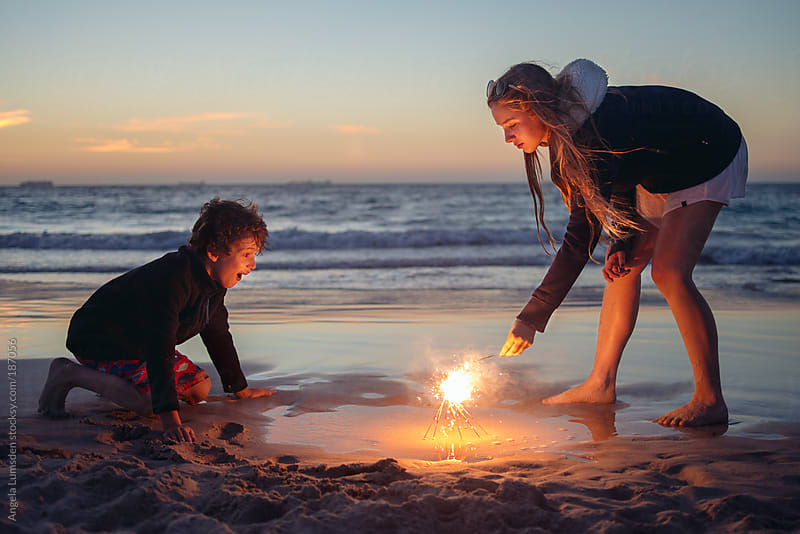 Children playing with sparklers at the beach at sunset by Angela Lumsden for Stocksy United