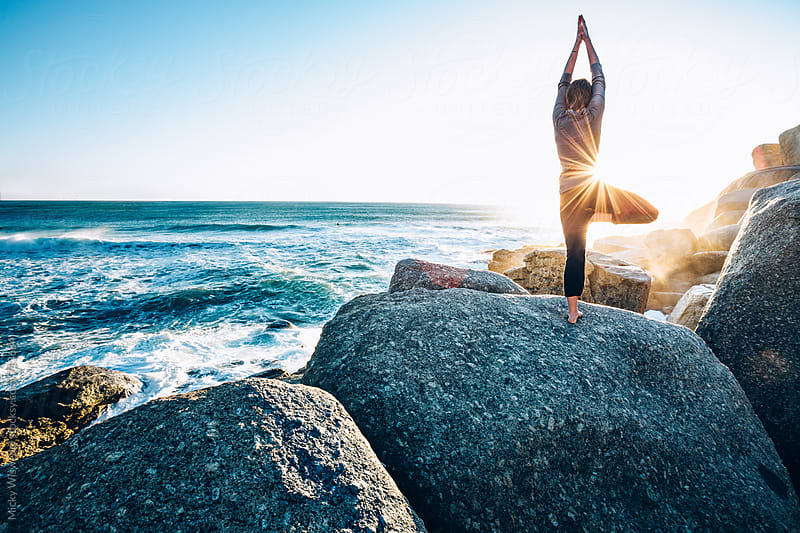 Fit young woman doing yoga on a rocky coast by Micky Wiswedel for Stocksy United