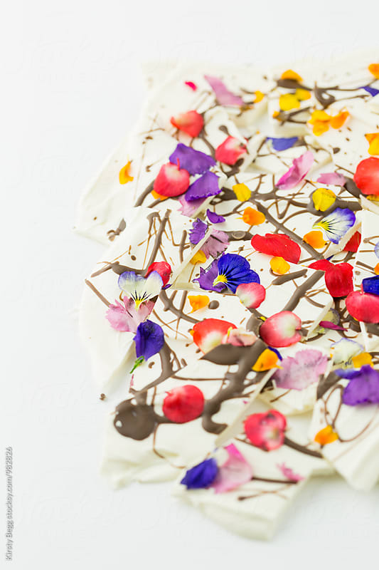 Shards of gourmet chocolate with edible flowers by Kirsty Begg for Stocksy United