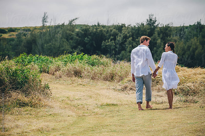 Couple talking and walking hand in hand down a grass road in Hawaii by Shelly Perry for Stocksy United