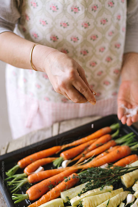Food: cooking oven roasted carrots and parsnip by Pixel Stories for Stocksy United