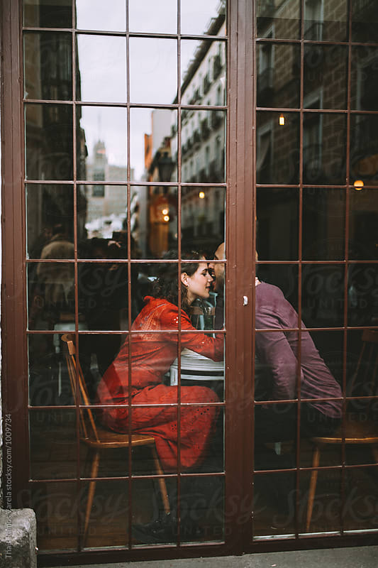 young couple chilling in a cafe by Thais Ramos Varela for Stocksy United