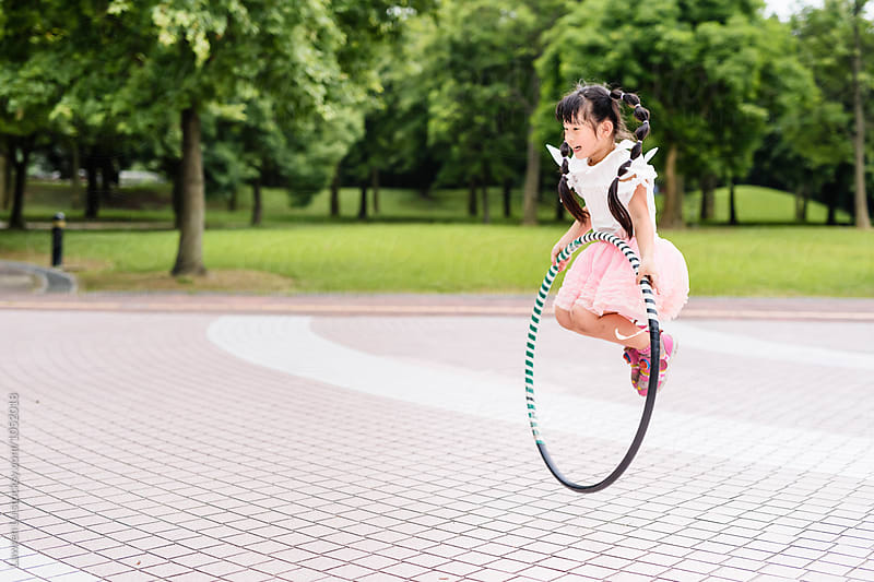 Happy Asian girl jumping with hulahoop by Lawren Lu for Stocksy United