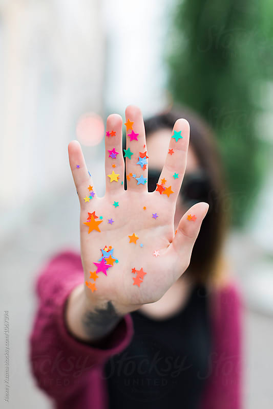 Young woman with color stars on her hand by Alexey Kuzma for Stocksy United
