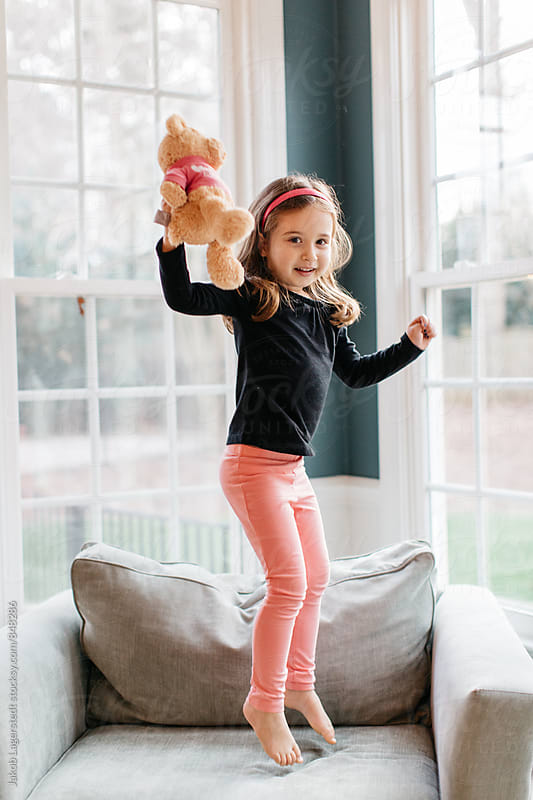 Cute young girl jumping with her teddy bear on a big chair by Jakob for Stocksy United