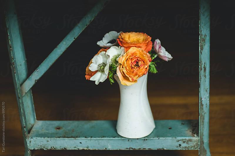 Vase of flowers on teal industrial metal platform by Tari Gunstone for Stocksy United