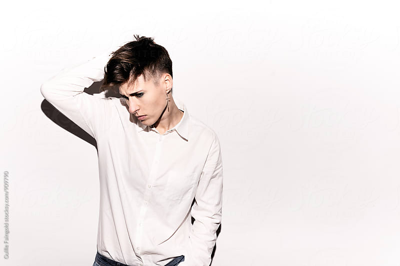 Model in white shirt posing on isolate background by Guille Faingold for Stocksy United