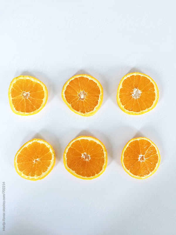 Slices of an orange on a white kitchen table - vertical by Marija Kovac for Stocksy United