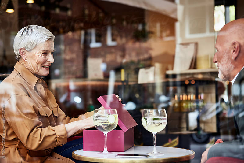 Senior Woman Opening Gift Box In Restaurant by ALTO IMAGES for Stocksy United