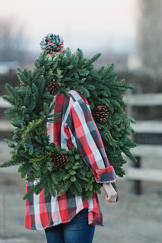 young woman carries evergreen wreath by Tana Teel for Stocksy United
