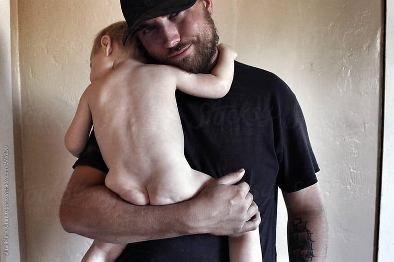 Proud Father Holding His Naked Child by Dina Giangregorio for Stocksy United