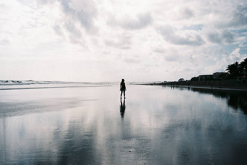 Woman walking on beautiful beach by Jacob Ammentorp Lund for Stocksy United