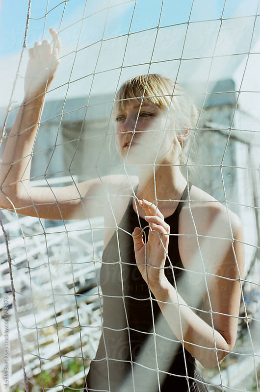 Young woman posing against net by Liubov Burakova for Stocksy United