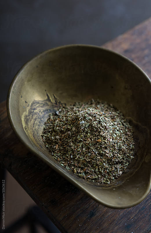Dried oregano in a brass bowl. by Darren Muir for Stocksy United