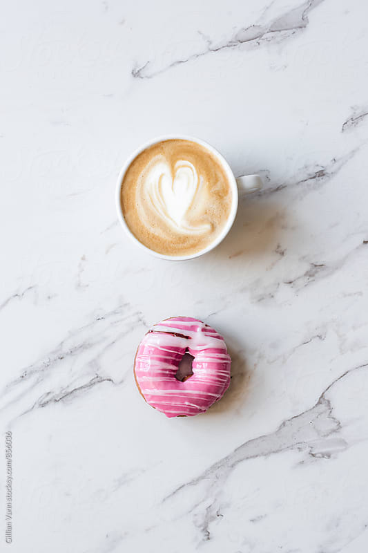 iced donut with striped pattern on a marble background by Gillian Vann for Stocksy United