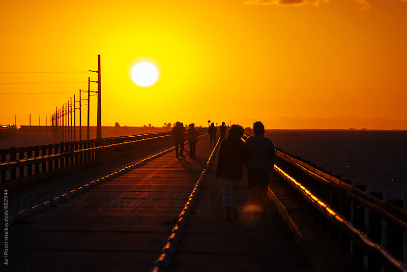 people walking towards sunset by Juri Pozzi for Stocksy United