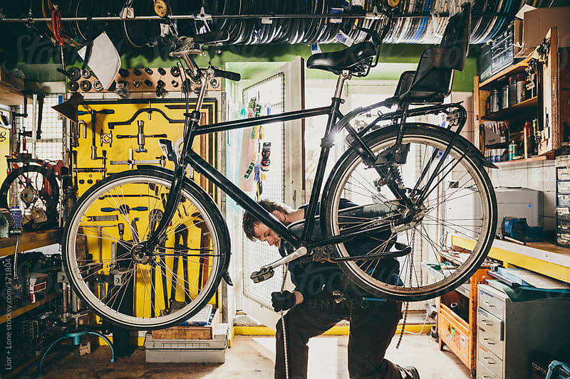 Young mechanic fixing the chain of a bicycle by Lior + Lone for Stocksy United