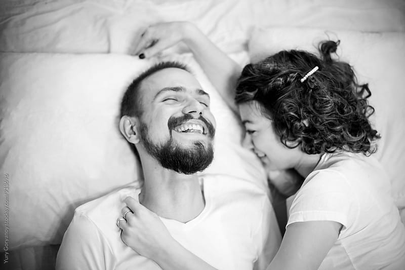 Portrait of laughing couple in bed. bw by Yury Goryanoy for Stocksy United