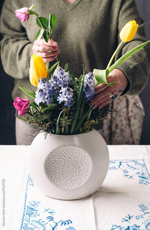 Woman arranging  flowers. by Darren Muir for Stocksy United