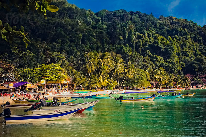 Tropical island bay with boats in the ocean and lush green jungle in Malaysia by Soren Egeberg for Stocksy United