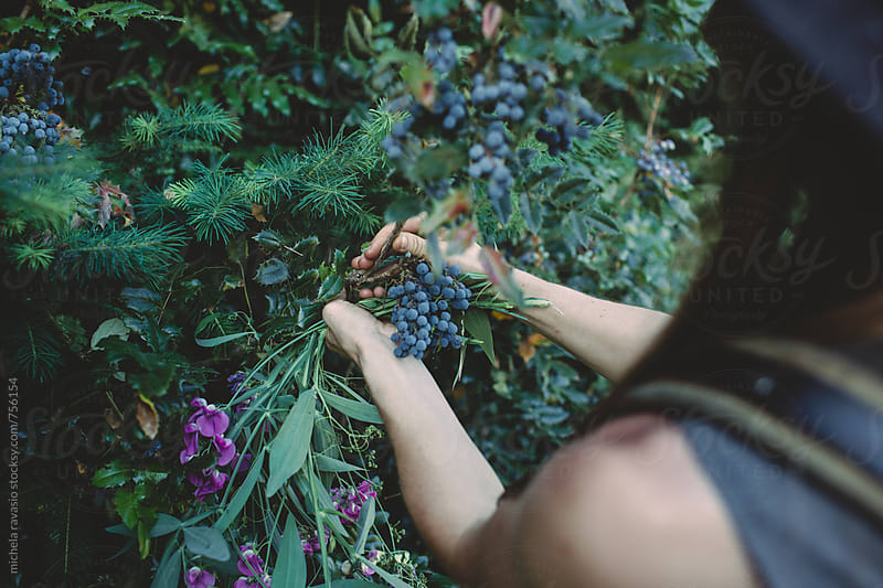 Young woman collecting plants for flower arrangement by michela ravasio for Stocksy United