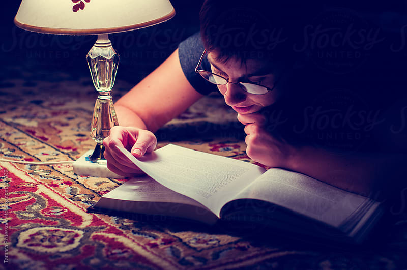Woman Reading Book By Lamplight On Rug by Tamara Pruessner for Stocksy United