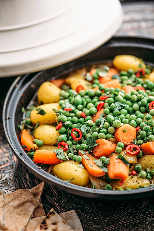 Food: Vegetarian Tagine with peas, potato, carrots and herbs  by Ina Peters for Stocksy United