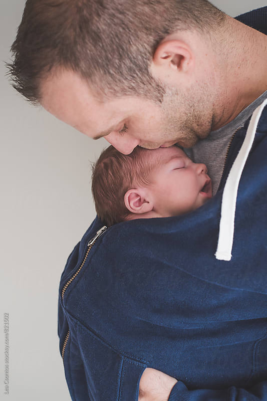 Father carrying his newborn son under his jumper and kissing his head by Lea Csontos for Stocksy United