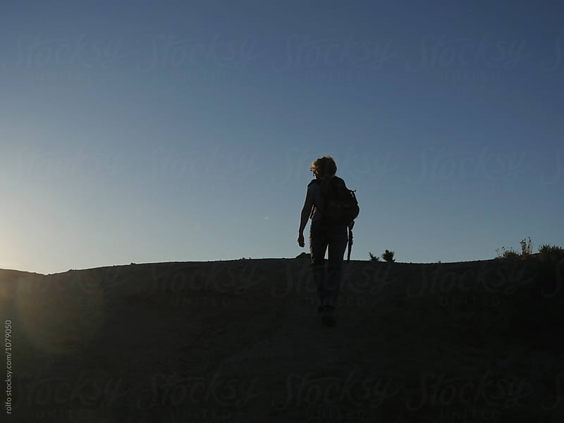 Female backpacker climbing up the hill by rolfo for Stocksy United