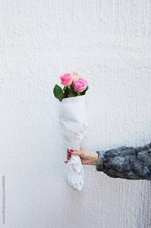 Woman holding a bouquet of roses by Jovana Rikalo for Stocksy United