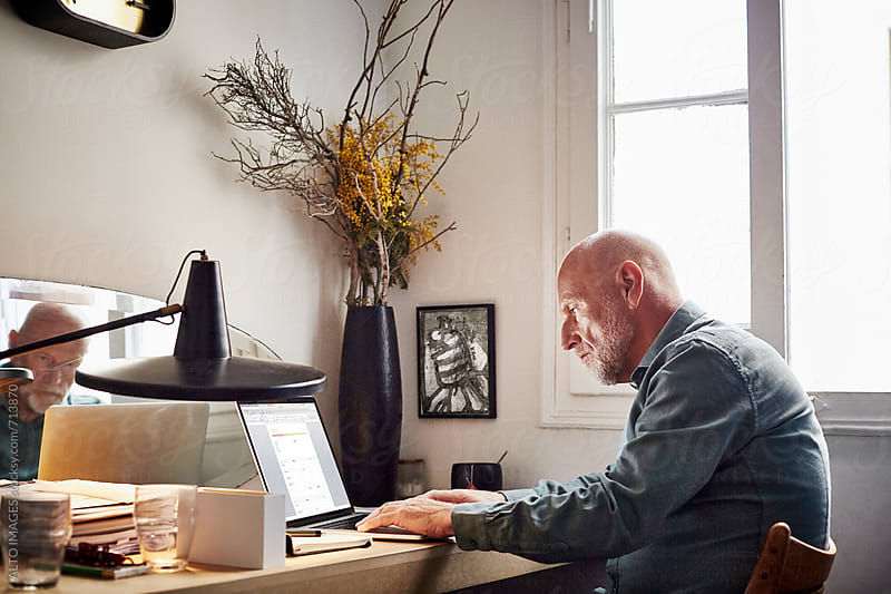 Confident Senior Businessman Using Laptop At Home by ALTO IMAGES for Stocksy United